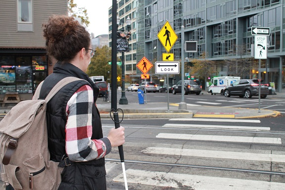 A young woman with a backpack stands at a complex intersection with her white cane.  There is a yellow pedestrain crossing sign and a crosswalk marked at the crossing.